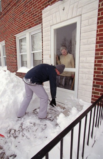 Mark Kaler, left, shuffles snow from the front door and sidewalk of Doris LaPaglia, who is over 70 years old, who lives at 4 Briarwood Road. Kaler has shuffled LaPaglia's sidewalk four times since Saturday. Kaler and his wife, Paulette, has shuffled their own sidewalk plus three other neighbors'. (Kenneth K. Lam/Baltimore Sun)