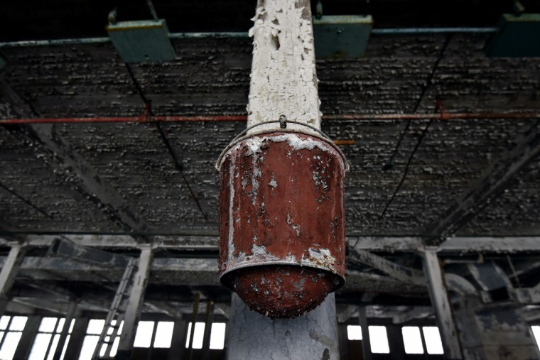 "Peeling paint on a fire bucket inside the Klots Throwing Company Mill, a silk mill in Lonaconing. The factory closed suddenly in 1957. Much of what was inside at the time still remains. Herb Crawford, who has owned the mill for 39 years, has been trying to keep the historic mill intact. The roof is in need of repair, but Crawford can only afford ""band-aid"" repairs. (Kim Hairston/Baltimore Sun)"