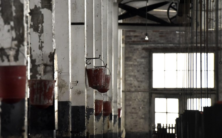 "Fire buckets hang from pillars in the Klots Throwing Company Mill, an abandoned silk mill in Lonaconing. The factory closed suddenly in 1957. Much of what was inside at the time still remains thanks to Herb Crawford, who has owned the mill for 39 years. Crawford has been trying to get help in preserving the last intact silk mill in the U.S.  The roof is in need of repair, but he can only afford ""band-aid"" repairs. (Kim Hairston/Baltimore Sun)"