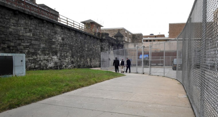 Corrections officials walk on the path leading to the closed Men's  Detention Center, seen behind the fence at right. At left is the old stone wall of the original penitentiary, the castle-like building that is now partly used as the Metropolitan Transition Center. (Amy Davis/Baltimore Sun)