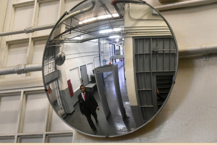 Public information officer Lt. Melvin Easley, a former guard at the Mens Detention Center, is reflected in a security mirror as he passes through the first floor south receiving area of the desolate Mens Detention Center. (Amy Davis/Baltimore Sun)