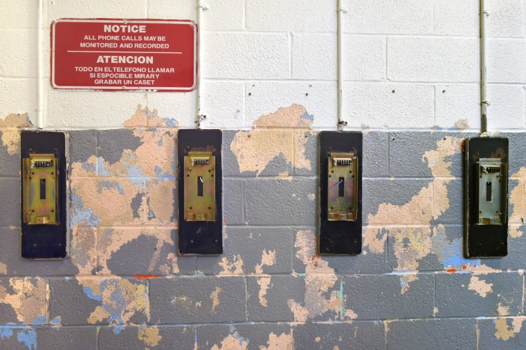 "The back plates for pay phones, available for use by inmates,are still affixed to the wall in the gym of the closed Men's  Detention Center. A sign warns: ""All phone calls may be monitored and recorded."" (Amy Davis/Baltimore Sun)"