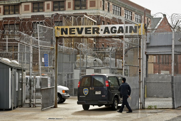 "A guard gets ready to secure the gate after a vehicle leaving the corrections complex passes under the ""Never Again,"" sign, a landmark seen by  all who exit. (Amy Davis/Baltimore Sun)"