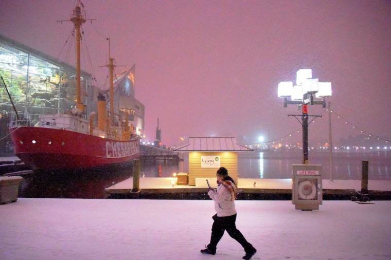 Andres Palestina of Baltimore walks at the Inner Harbor on his way home from work, taking photos as he walks past the ship Chesapeake while the East Coast is hit with a major blizzard this weekend. (Karl Merton Ferron / Baltimore Sun)