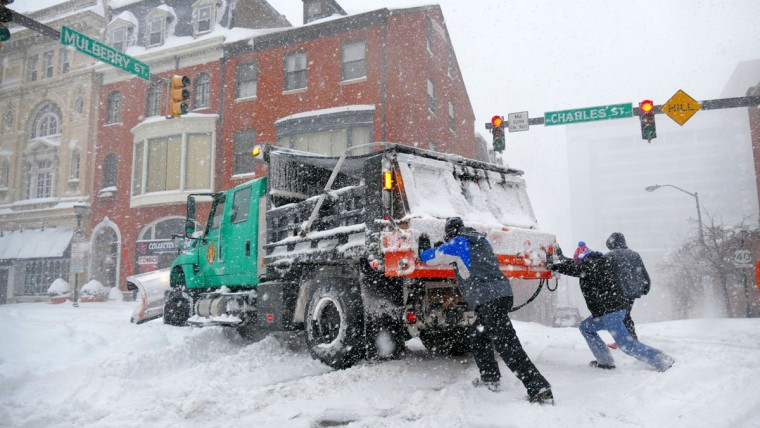 Chris Holder, left, and Chris Hauger try to push a loaded six-wheel dump truck and salt spreader that got stuck at Mulberry and Charles Streets. The Mount Vernon residents were not having much luck, as the truck can weigh upwards of 30,000 pounds while empty. It got stuck as a strong blizzard pummeled the region Saturday. (Karl Merton Ferron / Baltimore Sun)
