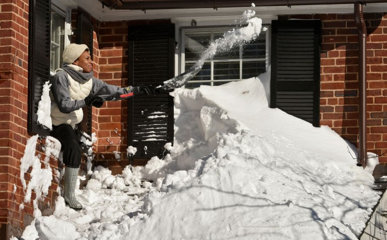 Apryl Doyle leans out her second floor window to shovel snow from her porch roof on Southfield Place in Homeland. The Baltimore region started digging out from a record snowstorm on Saturday. (Amy Davis / Baltimore Sun)