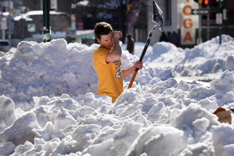 Rhett Reidpath, assistant manager at the Melting Pot restaurant in Towson, pauses as he shovels a path from the entrance to York Road. He said the snow was too compacted to use a snowblower. The restaurant will reopen tonight after being closed for two days. (Amy Davis / Baltimore Sun)