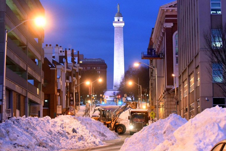 A front-end loader works to remove snow piles on Monument Street at Calvert before dawn on Tuesday. (Jerry Jackson/Baltimore Sun)