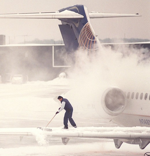 January 12, 1996 -- A Continental Airline employee sweeps snow off the wing of a MD-80 jet leaving BWI Airport for Houston, Texas this afternoon. The smoke is steam from a deicing spray that is applied to planes before takeoff. (Perry Thorsvik/Baltimore Sun)
