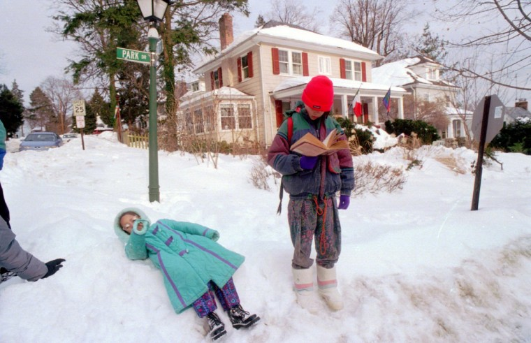 January 16, 1996 -- Ashley Johnson, 6, lies down momentarily in the snow and Ambrose Vandenbosche, 10, reads as they wait for the bus to take them to Powhatan Elementary School. They're at Park and Poplar Streets. (Algerina Perna/Baltimore Sun)