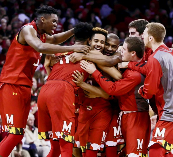 Maryland players rush to hug Maryland's Melo Trimble, third from left, after Trimble hit the game-winning basket against Wisconsin in the final seconds of an NCAA college basketball game Saturday, Jan. 9, 2016, in Madison, Wis. Maryland won 63-60. (Andy Manis/Associated Press)
