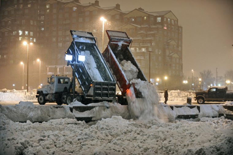February 9, 2010 -- Dump trucks filled with snow dumped their loads into the Inner Harbor at the end of Pier Five as another round of storm is expected to drop more snow on top of the already record level of snow in the Baltimore area. (Kenneth K. Lam/Baltimore Sun)