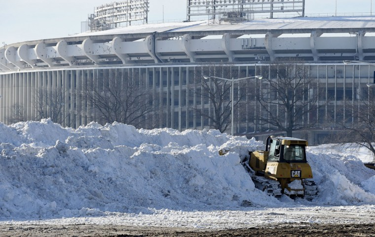 A vehicle pushes up pikes of snow after trucks dump their loads of snow in the parking lots of RFK Stadium in Washington, Monday, Jan. 25, 2016, as the nation's capital digs out following a monster weekend snow. (AP Photo/Susan Walsh)