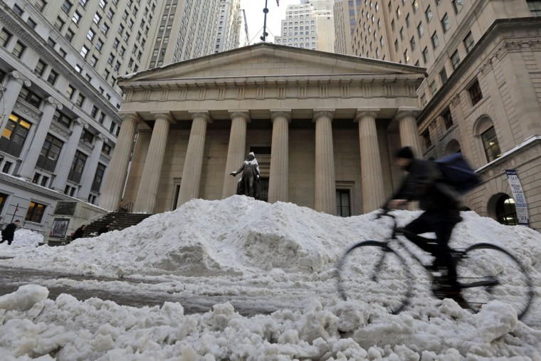 A bicyclist rides on Wall Street in front of Federal Hall in New York's Financial District, Monday, Jan. 25, 2016. East Coast residents who made the most of a paralyzing weekend blizzard face fresh challenges as the workweek begins: slippery roads, spotty transit service and mounds of snow that buried cars and blocked sidewalk entrances. (AP Photo/Richard Drew)