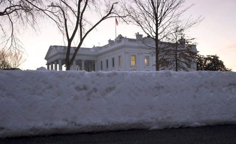 The White House peeks over plowed snow on the White House grounds in Washington, Monday, Jan. 25, 2016. East Coast residents who made the most of a paralyzing weekend blizzard face fresh challenges as the workweek begins: slippery roads, spotty transit service mounds of snow, and closed schools and government offices. (AP Photo/Carolyn Kaster)