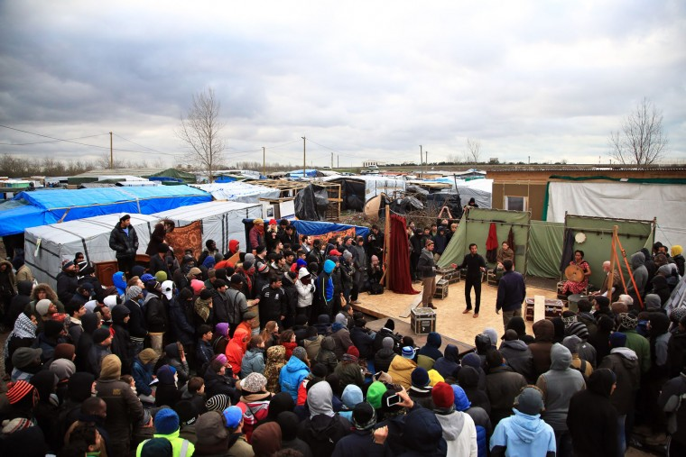 "Actors perform Hamlet Wednesday Feb. 3, 2016 in the refugees camp of Calais, northern France. The Globe theater company took ""Hamlet"" to Calais , bringing one of Shakespeare's best-known plays to an audience that almost certainly would rather see it in his native country. The play is hosted by the Good Chance theater in the heart of the camp, one of numerous structures set up by volunteers to fill the void for its displaced residents. (AP Photo/Thibault Camus)"