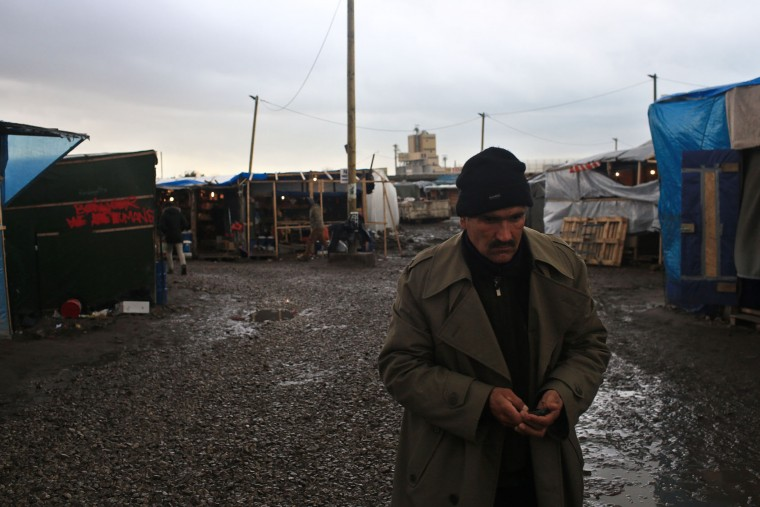 A migrant walks in the main street of the migrant camp of Calais, north of France, Thursday, Feb. 4, 2016. About 4,000 people from Syria, Sudan and other countries are estimated to be camped out in Calais as they try to reach Britain, some recently moving into new facilities but most still sleeping in what's been called Europe's biggest slum. (AP Photo/Thibault Camus)