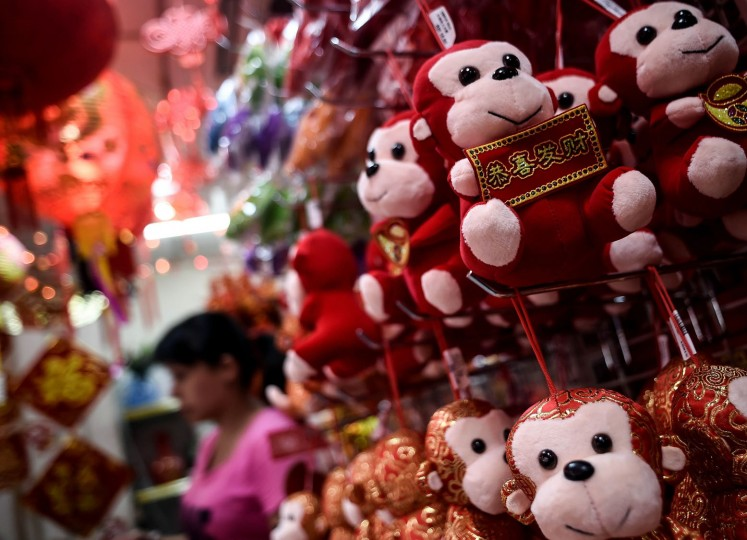 A shopkeeper walk past monkey soft-toys at a shop in Kuala Lumpur's popular Chinatown on February 5, 2016 ahead of the Lunar New Year celebrations. The Lunar New Year will mark the start of the year of the monkey on February 8. (Manan Vatsyayana/AFP/Getty Images)