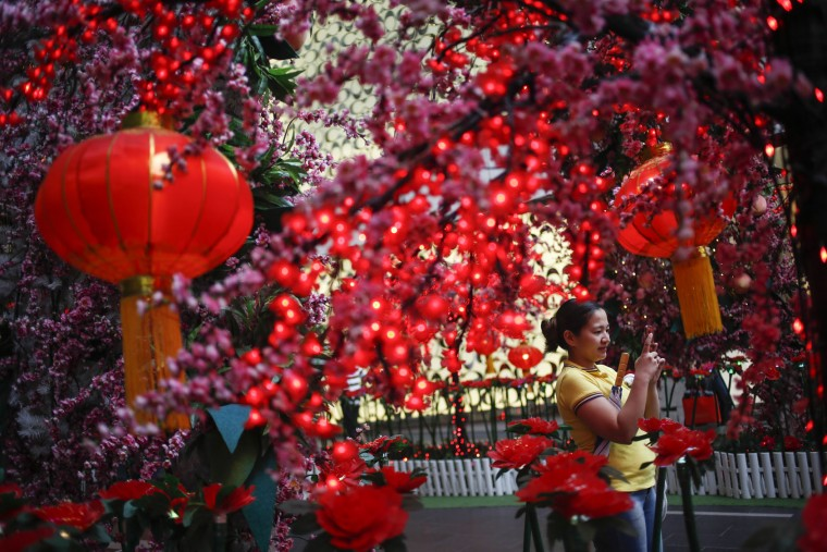 A Malaysian ethnic Chinese woman takes souvenir photographs in front of Lunar New Year decorations in Kuala Lumpur, Malaysia, Friday, Feb. 5, 2016. The Lunar New Year which falls on Feb. 8 this year marks the Year of the Monkey in the Chinese calendar. (AP Photo/Joshua Paul)
