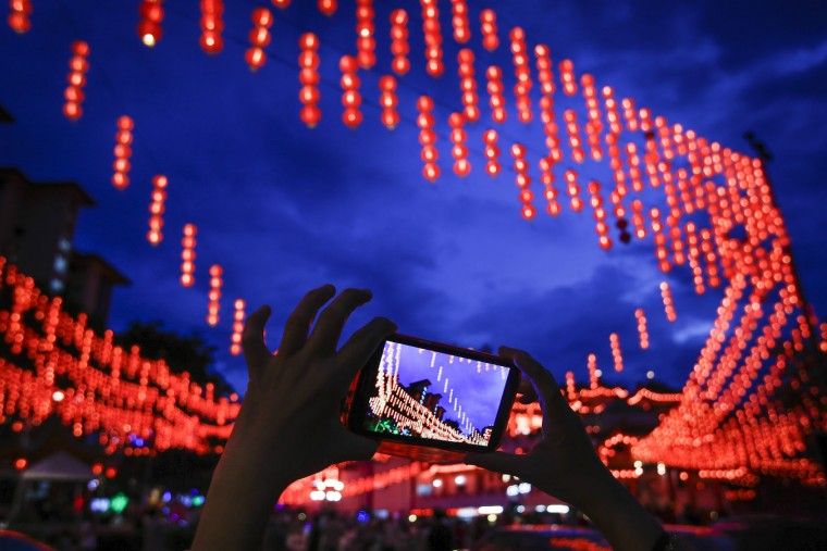 A Malaysian ethnic Chinese woman takes a souvenir photograph of illuminated traditional Chinese lanterns on the eve of Lunar New Year in Kuala Lumpur, Malaysia, Sunday, Feb. 7, 2016. The Lunar New Year which falls on Feb. 8 this year marks the Year of the Monkey in the Chinese calendar. (AP Photo/Joshua Paul)