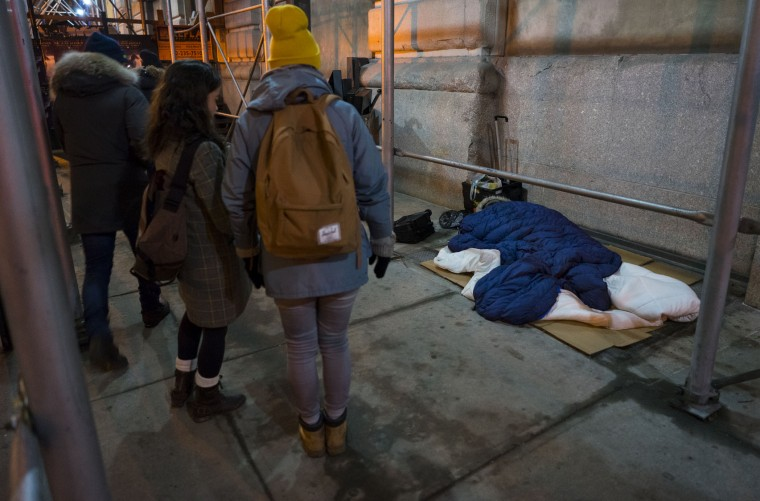 Alexis Sypek, center left, and Ashley Treni, center, both from New York and working with The Robin Hood Foundation, an organization that helps the poor, prepare to speak to a sleeping homeless person, right, during a count and survey of the homeless on the streets of New York early Tuesday, Feb. 9, 2016. Hundreds of people fanned out across the city to conduct the survey just after midnight. (AP Photo/Craig Ruttle)