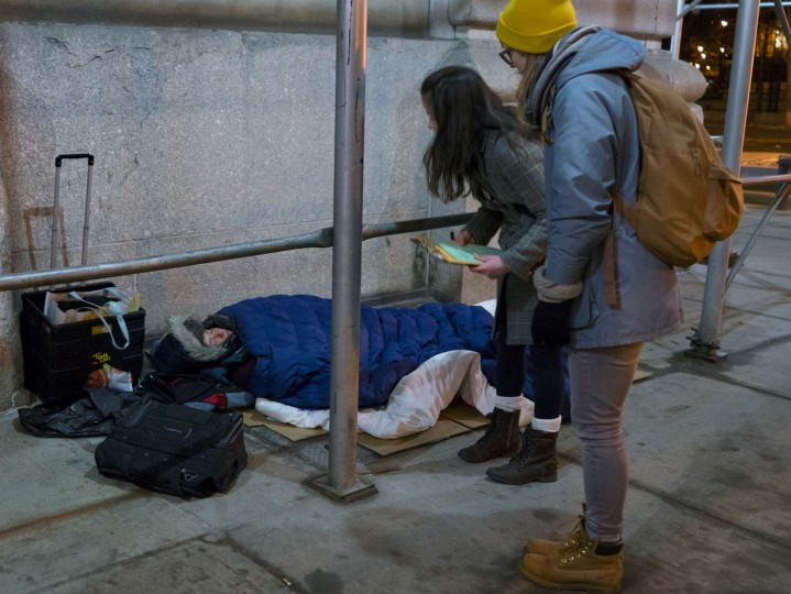 Alexis Sypek, center right, and Ashley Treni, far right, both from New York and working with The Robin Hood Foundation, an organization that helps the poor, speak to a homeless person during a count and survey of the homeless on the streets of New York early Tuesday, Feb. 9, 2016. Hundreds of people fanned out across the city to conduct the survey just after midnight. (AP Photo/Craig Ruttle)
