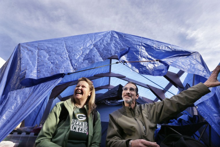 Elizabeth Nelson, left, sits with Paul Bultman as the two talk about living in tents under raised blue tarps in a city-sanctioned homeless encampment in Seattle on Tuesday, Feb. 9, 2016. Mayor Ed Murray has committed millions more dollars to expand shelter beds and social services. (AP Photo/Elaine Thompson)