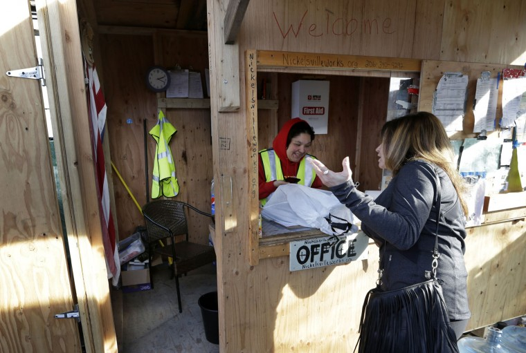 Desiree Hoffman, left, takes in a donation at a city-sanctioned homeless encampment, from a woman who lives in a nearby neighborhood in Seattle on Tuesday, Feb. 9, 2016. Seattle voters have agreed to tax themselves four separate times since 1986 to pay for affordable housing. The mayor recently proposed raising another $290 million with another housing levy on the November ballot. (AP Photo/Elaine Thompson)