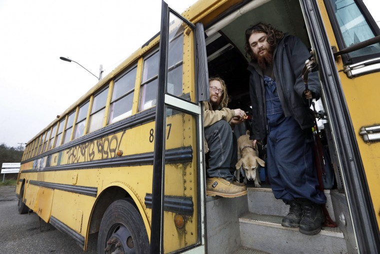 "Danny Fletcher, left, and Joshua Madrid stand in the doorway of a bus they share with three dogs in a temporary city-approved parking area for people living in their vehicles in Seattle. Fletcher, 32, who sleeps in his car at night, prefers the quiet of the parking zone to the harassment he faced in other parts of the city. ""We just want a safe place. Give us a safe place to park where neighbors won't harass us,"" he said. ""We're homeless. We're not diseased."" (AP Photo/Elaine Thompson)"
