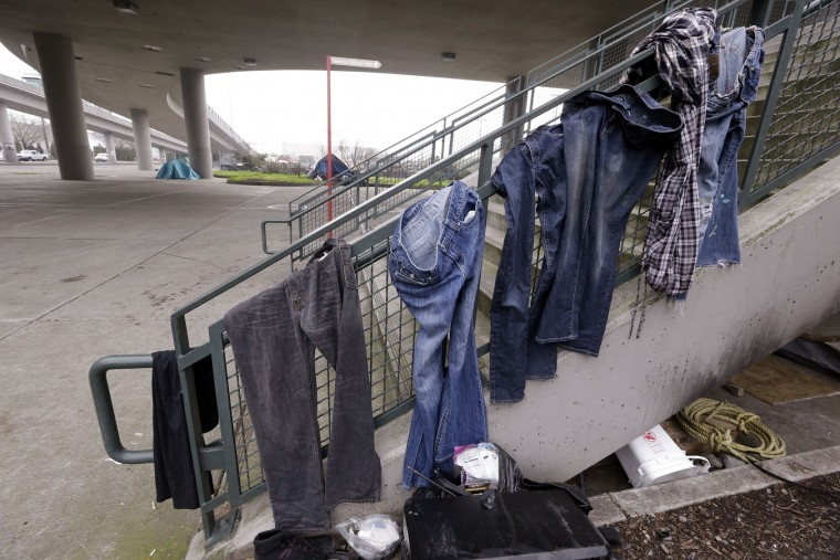 Clothing hangs from the handrail of stairs near the baseball stadium at a small homeless encampment in Seattle on Tuesday, Feb. 9, 2016. Mayor Ed Murray has committed millions of dollars to expand shelter beds and social services. (AP Photo/Elaine Thompson)