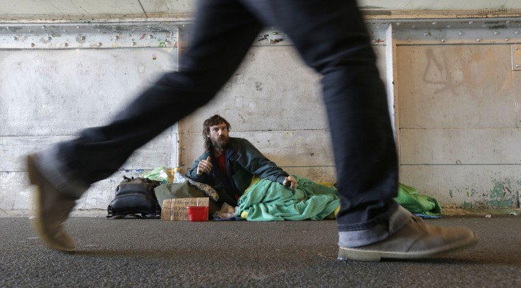 Harold McDuffie II, who says he has been homeless for three years, watches pedestrians pass by as he lies in a sleeping bag on a bridge leading to the ferry dock in downtown Seattle on Tuesday, Feb. 9, 2016. Seattle has the third-highest number of homeless people in the U.S. (AP Photo/Ted S. Warren)