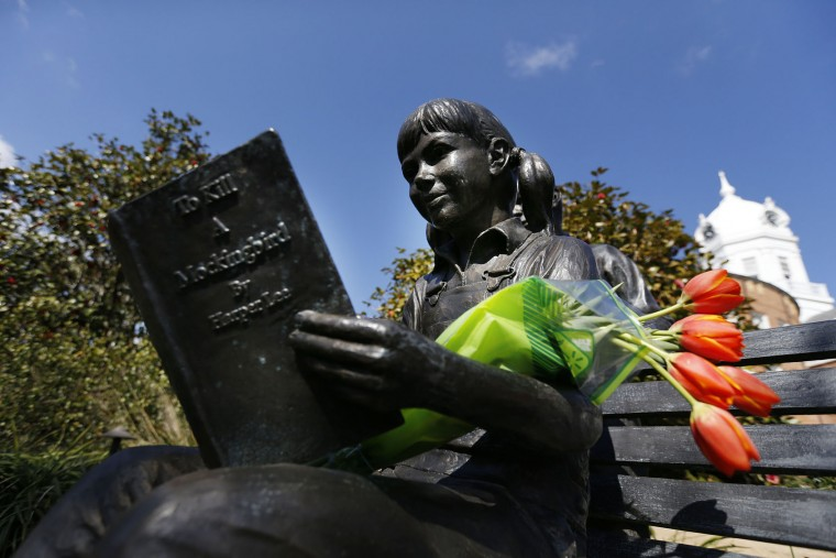 "Flowers are placed on a statue of a girl reading Harper Lee's ""To Kill a Mockingbird,"" in memorial of Lee, Friday, Feb. 19, 2016, in Monroeville, Ala. Lee, the elusive author of the best-selling classic, died Friday, according to her publisher Harper Collins. She was 89. (AP Photo/Brynn Anderson)"