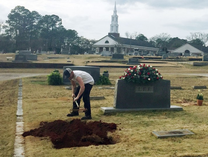 "A man rakes soil over a grave in the Lee family cemetery plot, Saturday, Feb. 20, 2016, in Monroeville, Ala. Harper Lee, the author of ""To Kill a Mockingbird,"" died Friday, Feb. 19, 2016. She was 89. (AP Photo/Kim Chandler)"