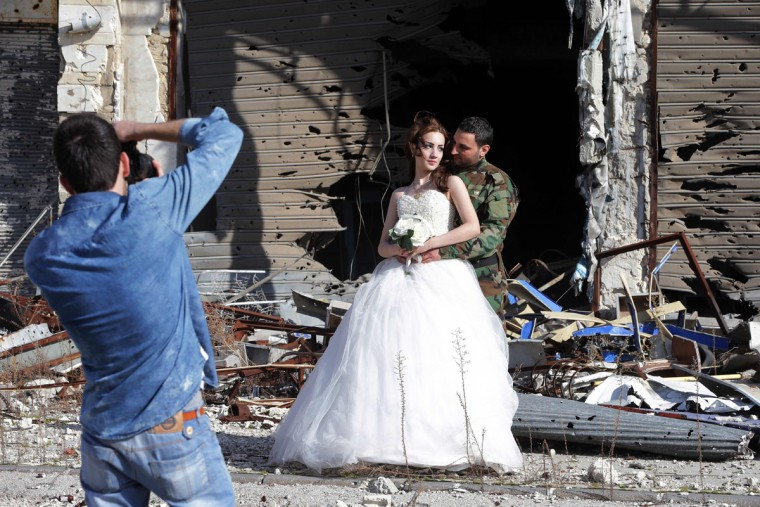 Newly-wed Syrian couple Nada Merhi, 18, and Hassan Youssef, 27, have their wedding pictures taken in front of a heavily damaged building in the war ravaged city of Homs on February 5, 2016. A Syrian photographer thought of using the destruction of Homs to take pictures of newly wed couples to show that life is stronger than death. (Joseph Eid/AFP/Getty Images)