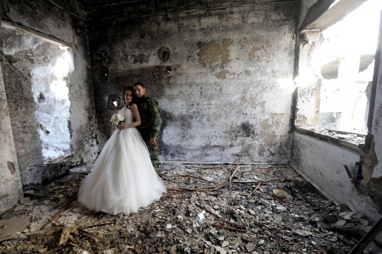 Newly-wed Syrian couple Nada Merhi, 18, and Hassan Youssef, 27, have their wedding pictures taken in a heavily damaged building in the war ravaged city of Homs on February 5, 2016. A Syrian photographer thought of using the destruction of Homs to take pictures of newly wed couples to show that life is stronger than death. (Joseph Eid/AFP/Getty Images)