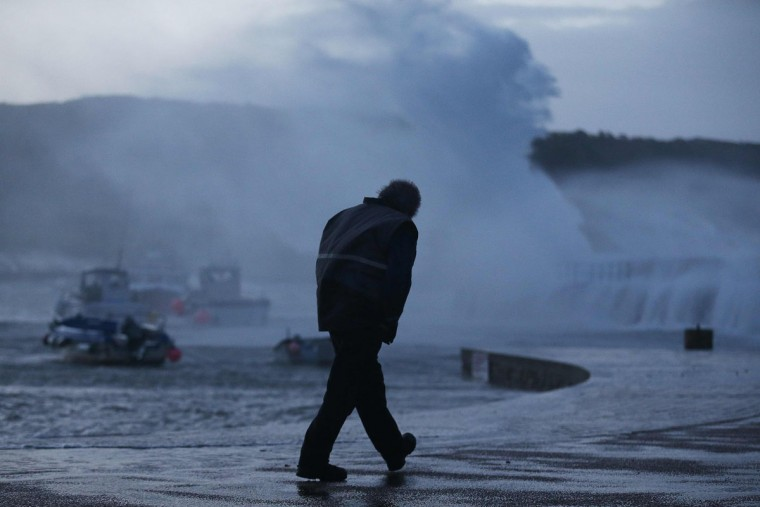 A man walks past anchored boat in a harbor in Auderville, northwestern France, on February 8, 2016, as strong winds hit the region. Winds of over 130 kh/h were recorded in the region where 16 departments have been placed under alert for for wind and flooding waves. (CHARLY TRIBALLEAU/AFP/Getty Images)