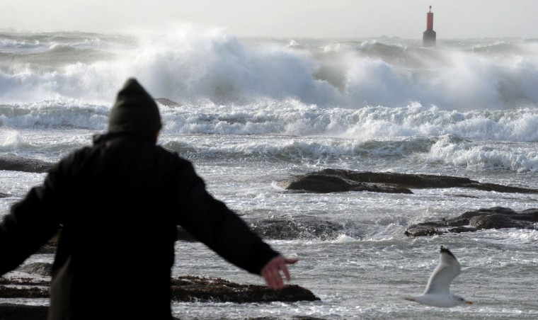A man look at waves breaking against the Le Guilvinec harbor pier in the western of France on February 8, 2016. (FRED TANNEAU/AFP/Getty Images)
