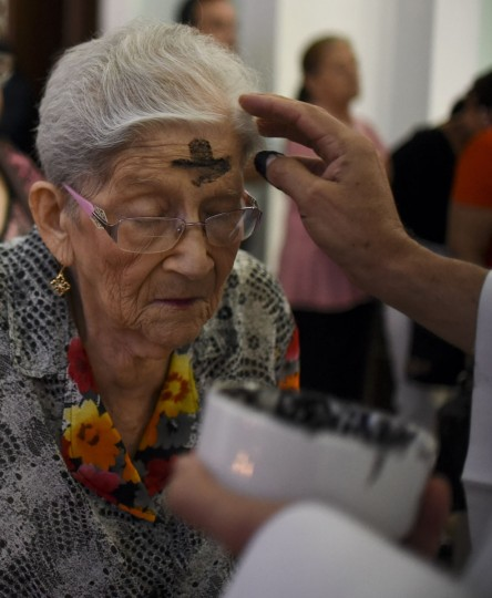 A Catholic faithful participates in a mass for Ash Wednesday on February 10, 2016, in Cali, Colombia. Ash Wednesday marks the beginning of Lent, a period of penitence for Christians before Easter. (AFP Photo/Luis Robayo)