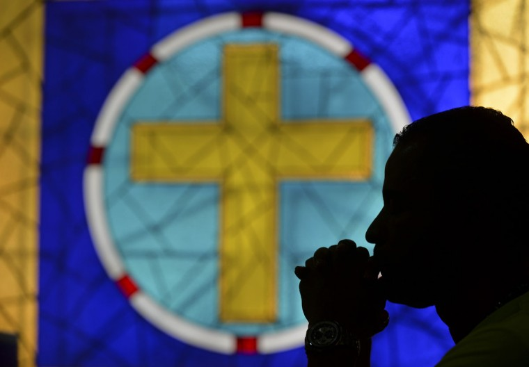 A Catholic faithful prays during Ash Wednesday on February 10, 2016, in Cali, Colombia. Ash Wednesday marks the beginning of Lent, a period of penitence for Christians before Easter. (AFP Photo/Luis Robayo)