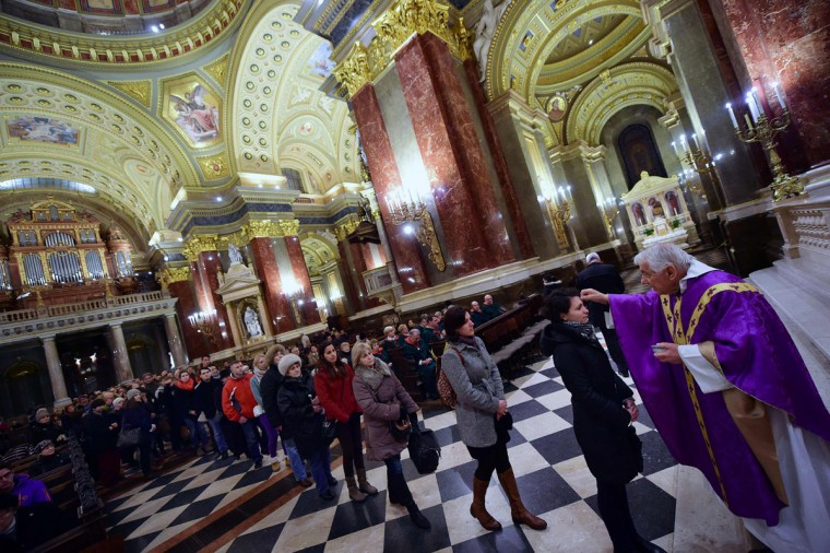 Local beleivers receive the ash-cross, given by father Attila Farkas (R) during a mass in the St Stephan Basilica at the beginning of Lent, which starts 40 days before Easter on February 10, 2016 during an evening mass for Ash Wednesday in Budapest, Hungary. (AFP Photo / Attila Kisbenedek)