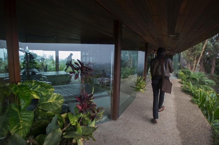 A visitor passes guest bedrooms with glass-walled views. (DAVID MCNEW/AFP/Getty Images)