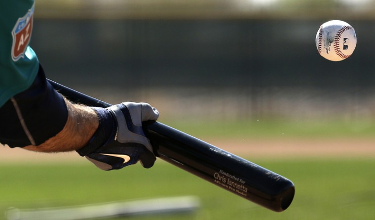 Seattle Mariners' Chris Iannetta bunts during spring training baseball practice Saturday in Peoria, Ariz. (Charlie Riedel/AP)