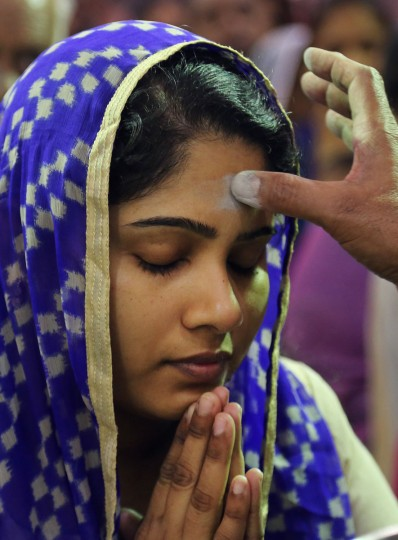 A Roman Catholic priest marks a sign of the cross on the forehead of an Indian Catholic worshipper in observance of Ash Wednesday at the St. Joseph Cathedral in Hyderabad, India, Wednesday, Feb. 10, 2016. The Ash Wednesday marks the beginning of Lent, a solemn period of 40 days of prayer and self-denial leading up to Easter. (AP Photo/Mahesh Kumar A.)
