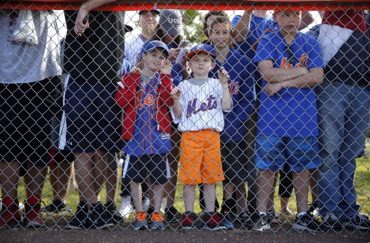 Fans watch as the New York Mets take the field during spring training baseball practice Friday in Port St. Lucie, Fla. (Jeff Roberson/AP)