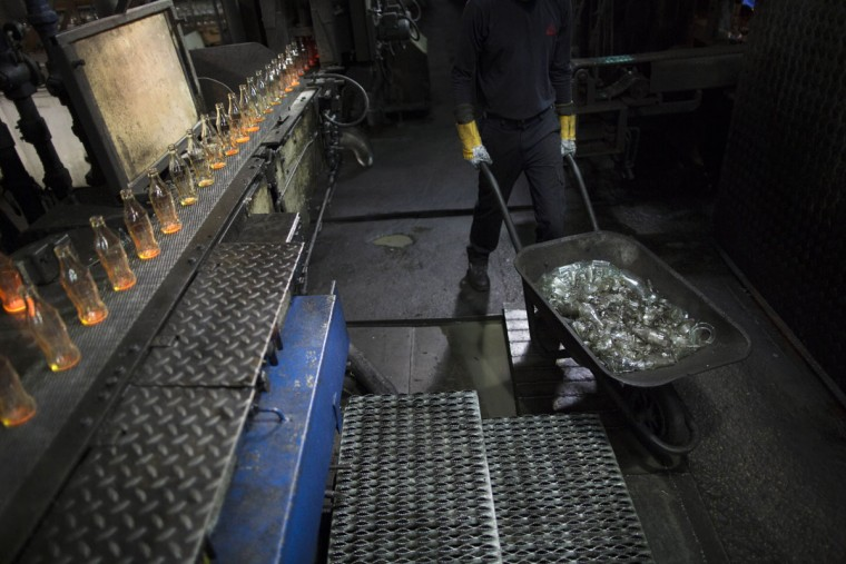 In this Tuesday, Jan. 26, 2016 photo, a worker pushes a wheelbarrow with broken glass bottles at the Phoenicia Glass Works Ltd. factory in the southern Israeli town of Yeruham. Factory workers grind these rejects into shards and pile them outside. Recycled glass bottles from across the country are sent here and ground up, too. The glass pieces are shoveled into the ovens to be fired into new glass bottles. Sand, the basic ingredient of glass, is hauled in from a nearby desert quarry. (AP Photo/Oded Balilty)
