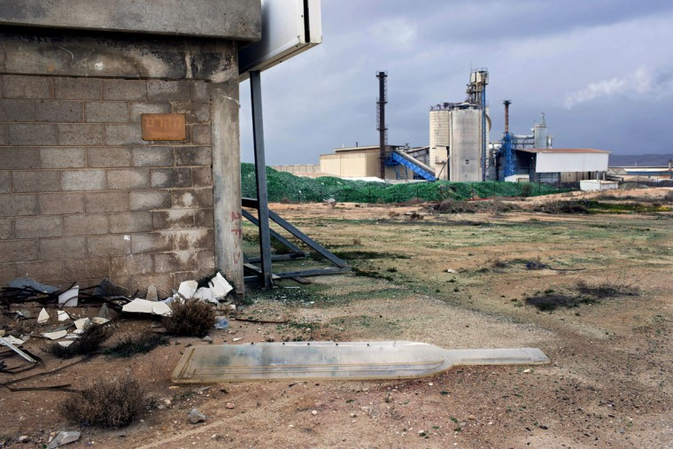 In this Tuesday, Jan. 26, 2016 photo, a broken sign lies on the ground at the Phoenicia Glass Works Ltd. factory in the southern Israeli town of Yeruham. Phoenicia Glass Works Ltd. produces a million bottles and containers a day for beverage giants Coca Cola, Pepsi, and Heineken, as well as Israeli wineries and olive oil companies. Every day, about 300,000 bottles come out of the ovens with defects. (AP Photo/Oded Balilty)