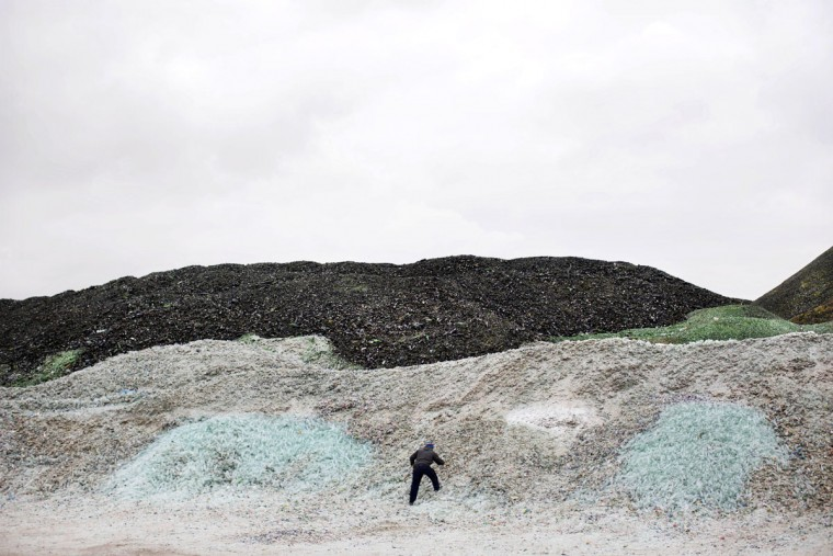 In this Wednesday, Jan. 27, 2016 photo, a worker collects plastic bottles among piles of broken glass, later to be recycled at the Phoenicia Glass Works Ltd. factory in the southern Israeli town of Yeruham. Phoenicia Glass Works Ltd., Israelís only glass container factory, produces one million containers a day. Some 300,000 bottles a day come out with defects, and the factory grinds them into shards and piles them in a desert lot to be melted into new bottles. The factory is in the middle of the desert, and works round the clock, every day of the year. (AP Photo/Oded Balilty)