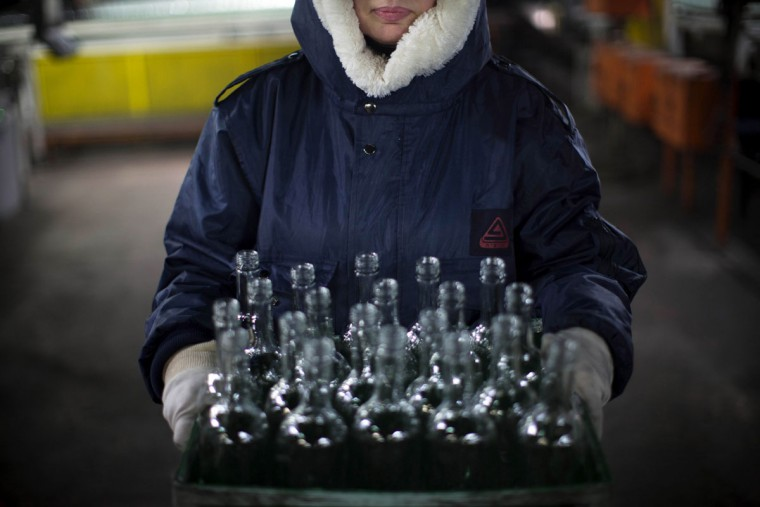 In this Wednesday, Jan. 27, 2016 photo, an employee carries a box of defective glass bottles to be recycled at the Phoenicia Glass Works Ltd. factory in the southern Israeli town of Yeruham. Factory workers grind these rejects into shards and pile them outside. Recycled glass bottles from across the country are sent here and ground up, too. The glass pieces are shoveled into the ovens to be fired into new glass bottles. Sand, the basic ingredient of glass, is hauled in from a nearby desert quarry. (AP Photo/Oded Balilty)