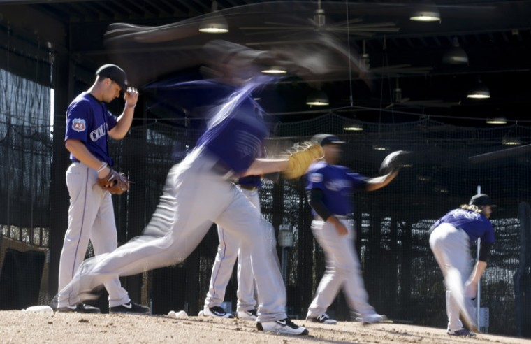 Colorado Rockies pitchers throw during spring training baseball practice in Scottsdale, Ariz., on Monday. (Chris Carlson/AP)