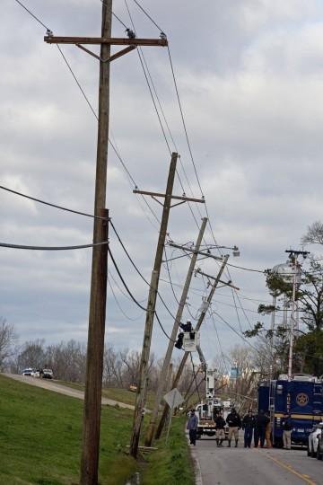 Utility crews repair fallen power lines on Louisiana highway 44 in front of the Sugar Hill RV Park in Convent, La., Wednesday, Feb. 24, 2016. The RV Park was seriously damaged the day before by a tornado. (AP Photo/Max Becherer)
